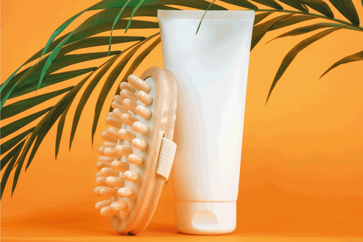 White blank cosmetic tube of cream or body lotion, orange fruit, wooden anti-cellulite massager and green branch palm