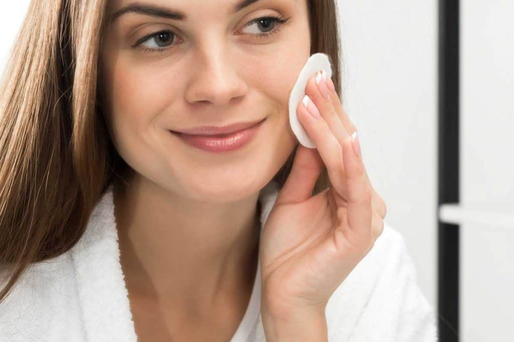 Woman cleaning face with cotton pad, How To Remove Sunscreen From Your Face - Even Without Cleanser