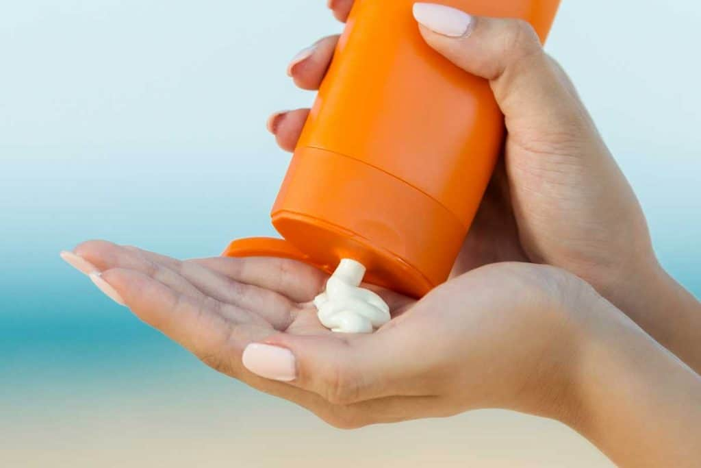 Woman hand apply sunscreen on the beach, 10 Best Moisturizer With Sunscreen For Oily Skin