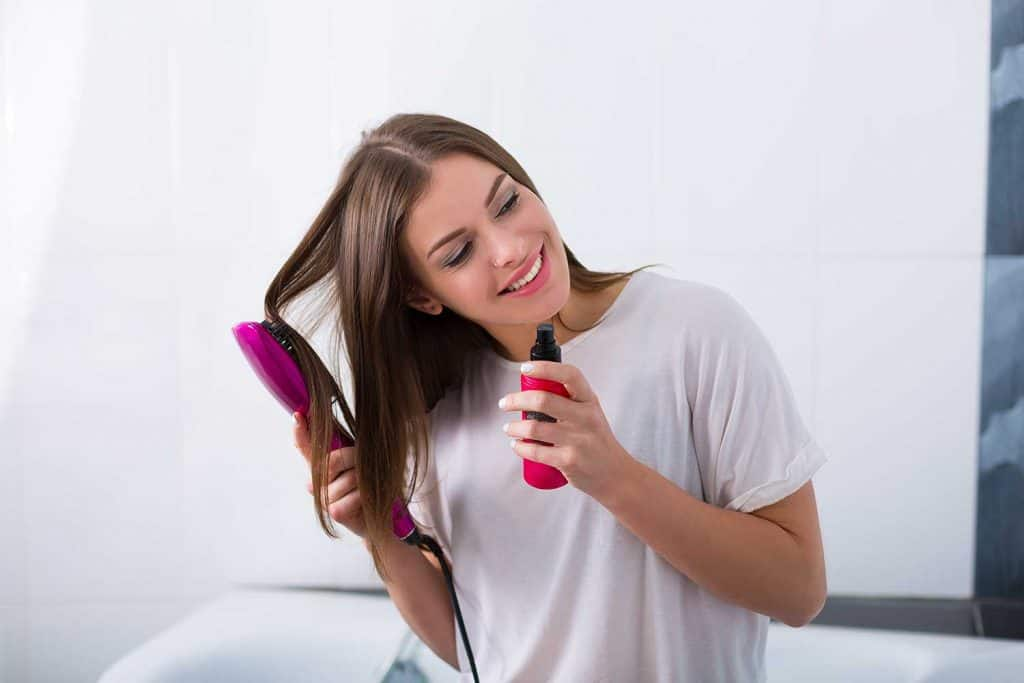 Woman using a hot brush to straighten her hair