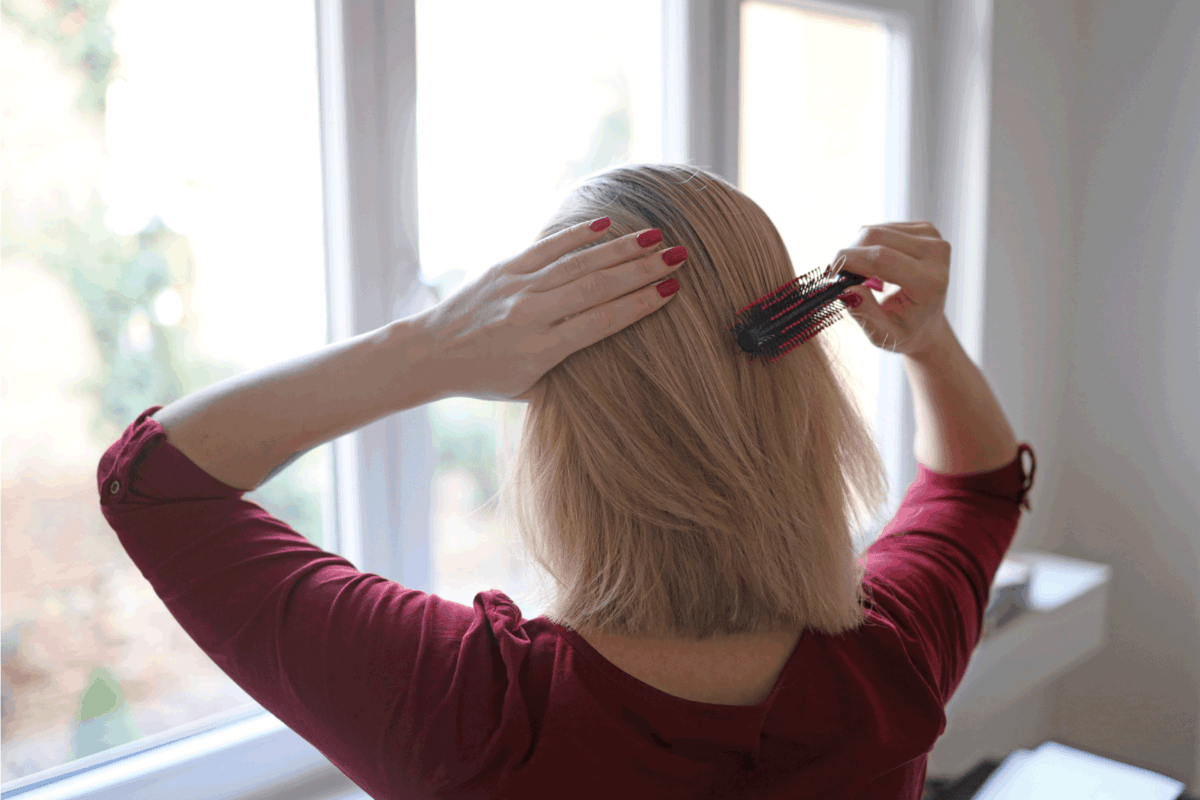 Young woman combing long blond hair by the window