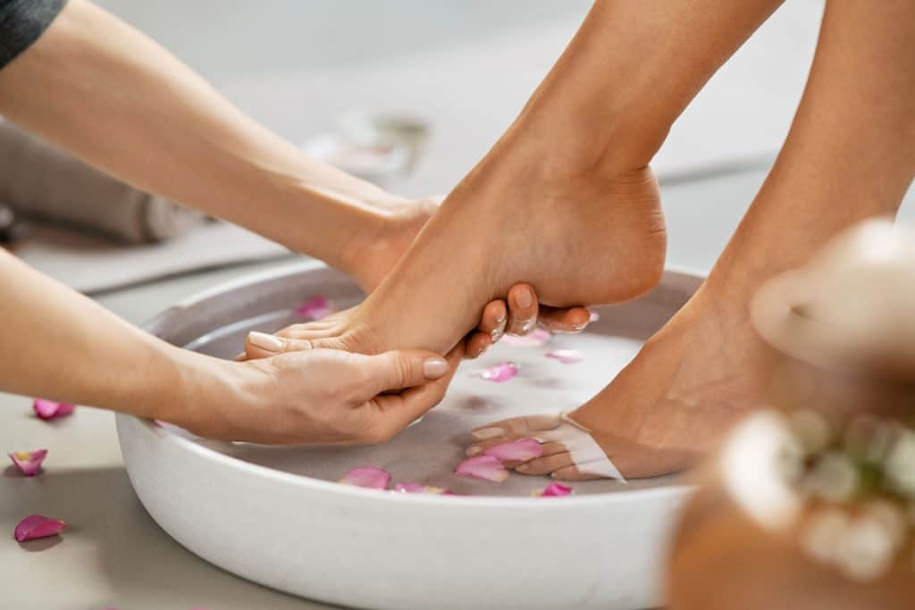Young woman having her feet scrubbed in beauty salon