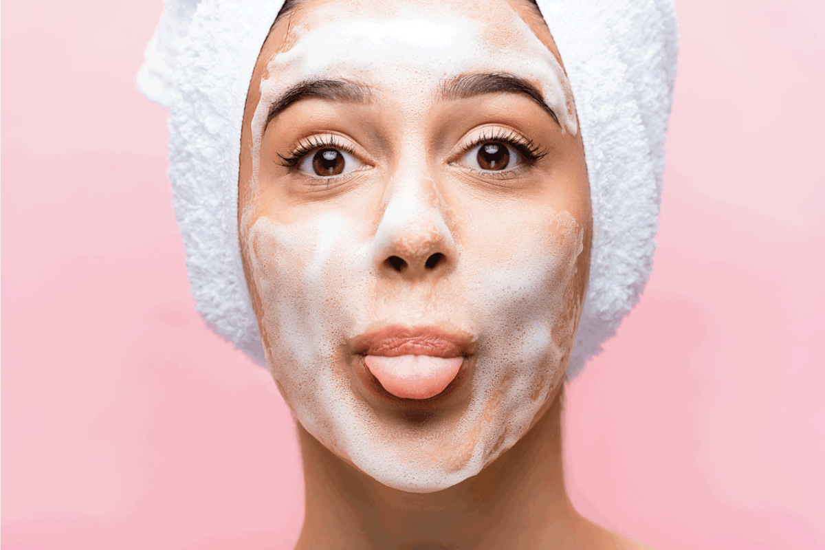 beautiful woman with towel on hair and foam on face showing tongue isolated on pink