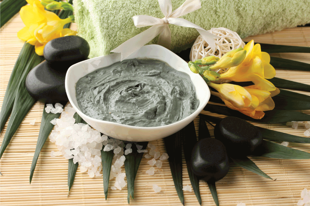 green colored cosmetic clay in a ceramic bowl on a bamboo mat with hot stone and towel. How Long Should You Keep A Clay Face Mask On