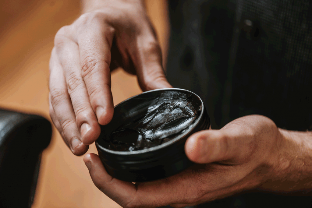 man holding jar with black hair pomade. What Can I Use Instead Of Hair Mousse [6 Alternatives]