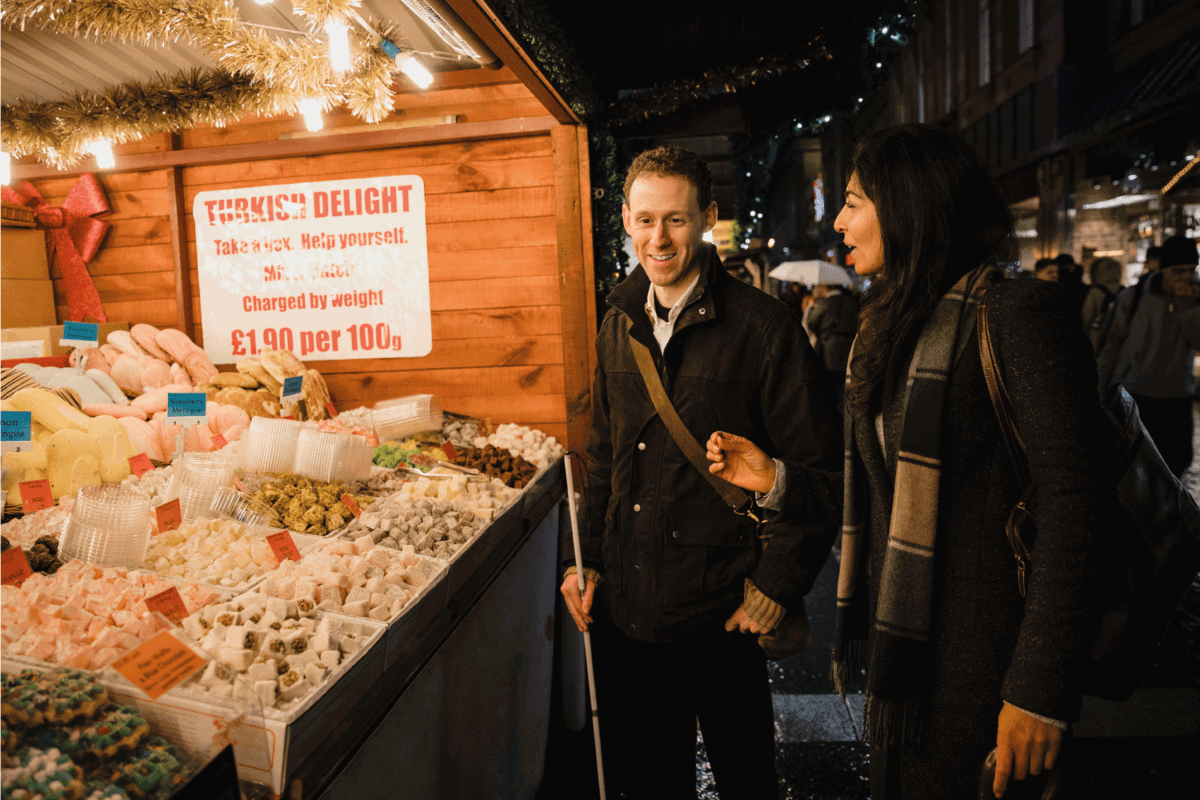 man standing beside a woman at a sweets stall on a night market wearing business casual with crossbody bag