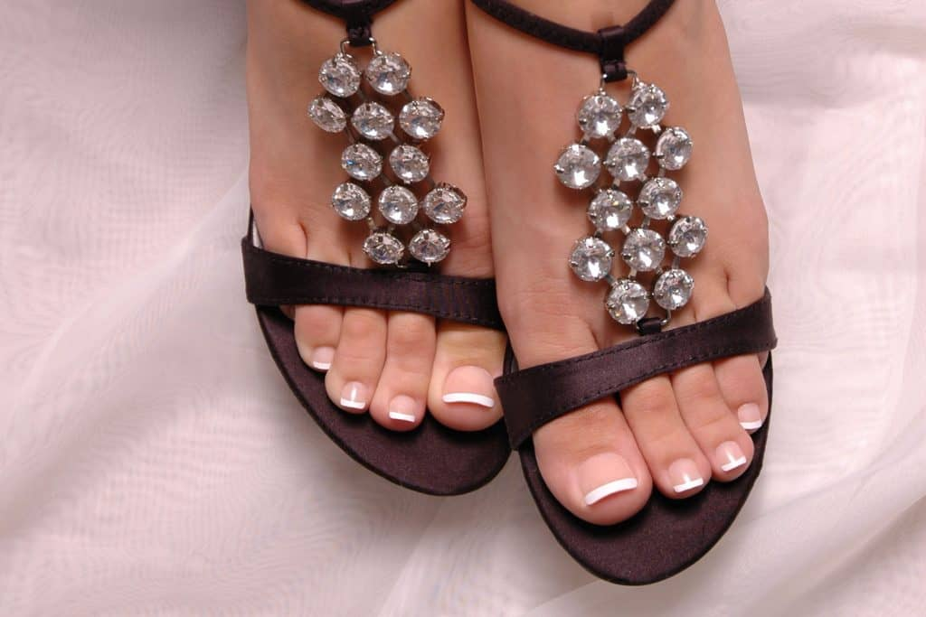Woman's feet with french pedicure wearing stilletos