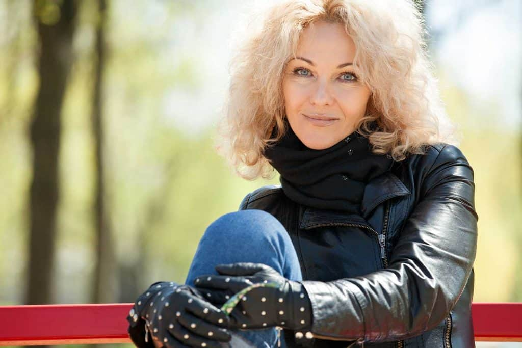 45 year old blonde woman with curly hair in a black leather jacket