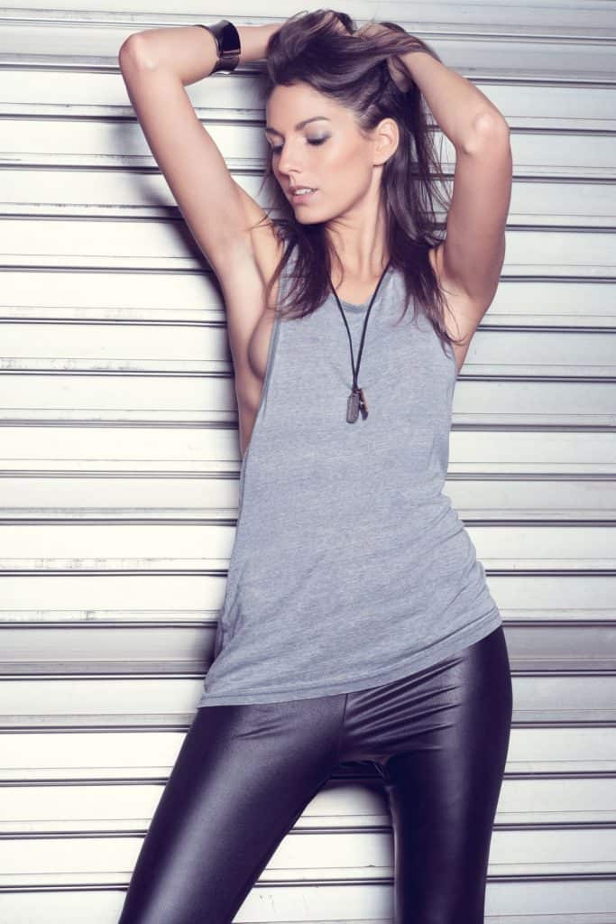 A beautiful woman posing wearing a leather shirt and faux leather pants