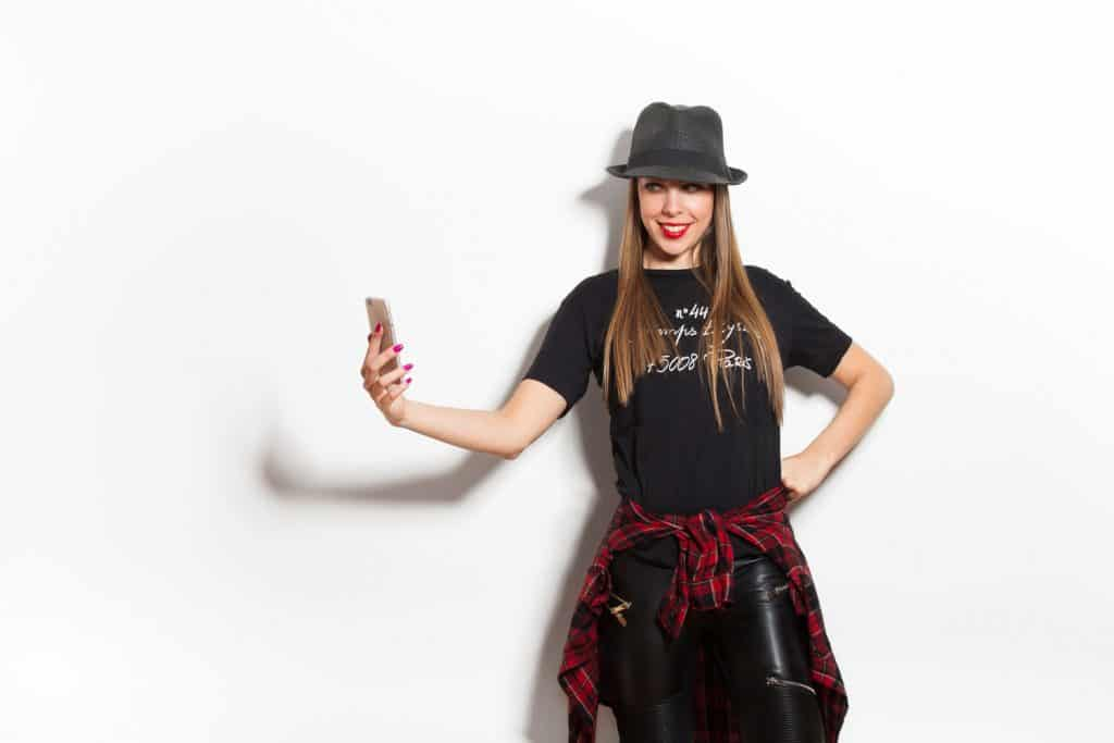 A beautiful woman taking a selfie wearing a black leather faux pants on a white background