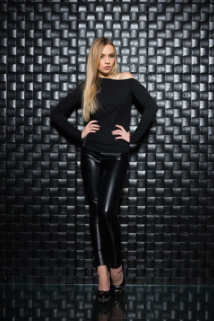 A beautiful woman wearing a black long sleeve shirt and faux leather pants on a black background