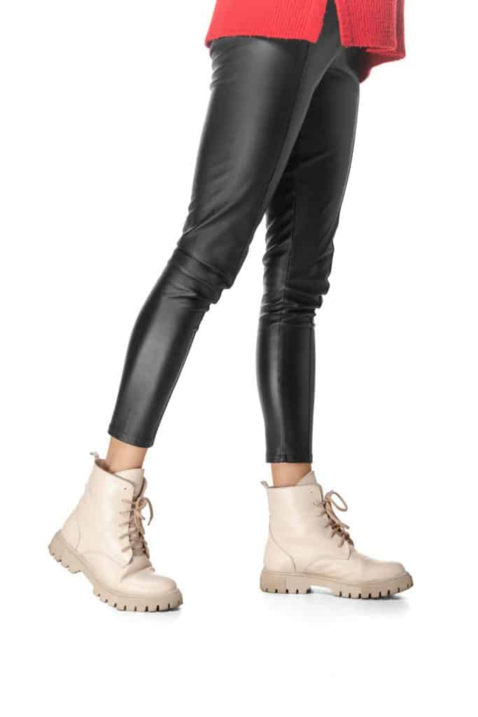 A photo of a woman wearing a faux leather pants and white boots