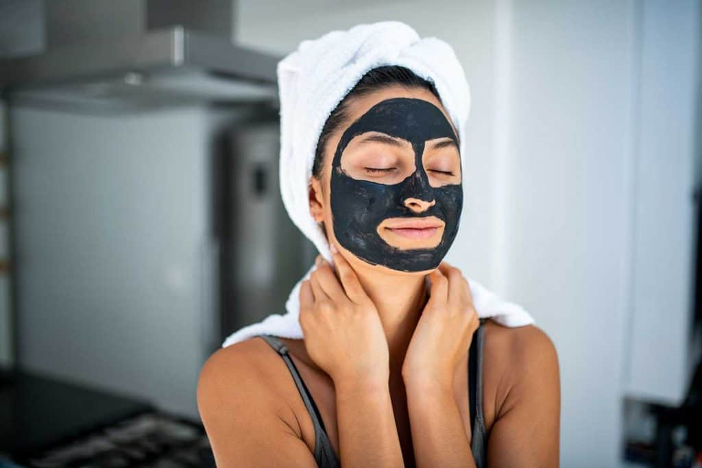 A smiling woman using beauty treatment at home