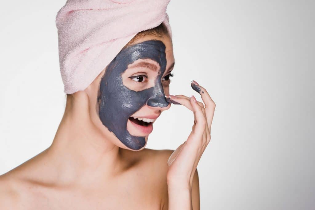 A woman applying clay mask on her face on a white background
