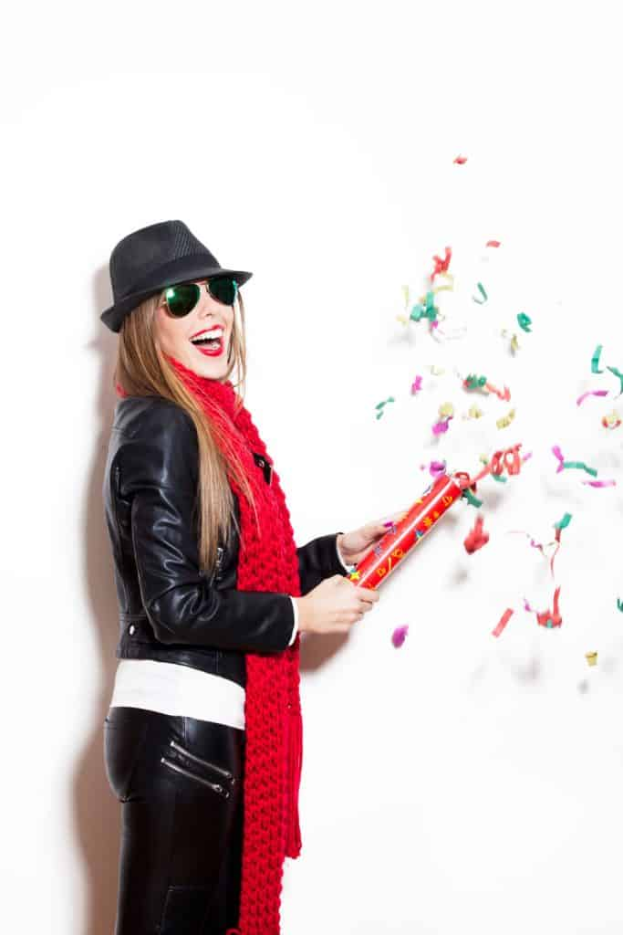 A woman opening a confetti wearing a leather jacket and faux leather pant