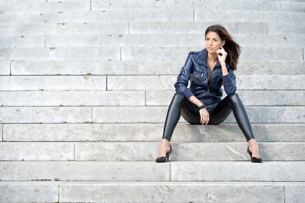A woman sitting on the stairs wearing a leather denim jacket and faux leather pants