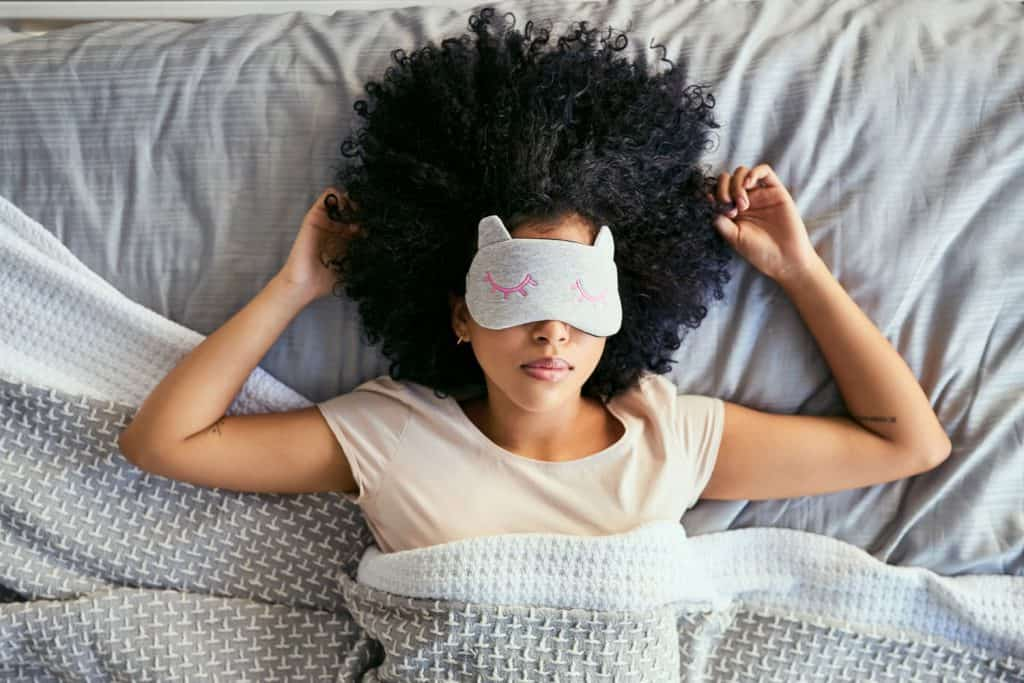 A woman sleeping with her eye mask on, How To Use A Gel Bead Eye Mask