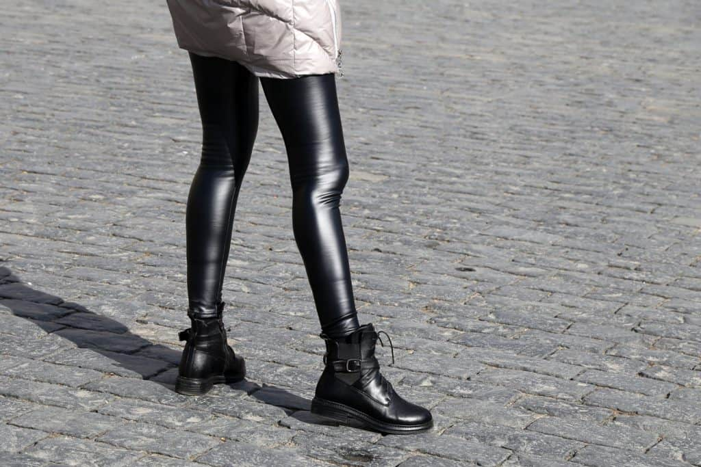 A woman wearing a faux leather pants and black leather boots