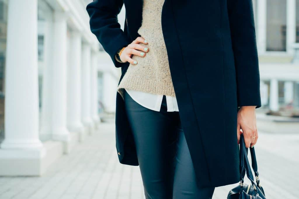 A woman wearing a formal sweater and tight blue leggings, What Tops To Wear With Leggings [Including For Work]