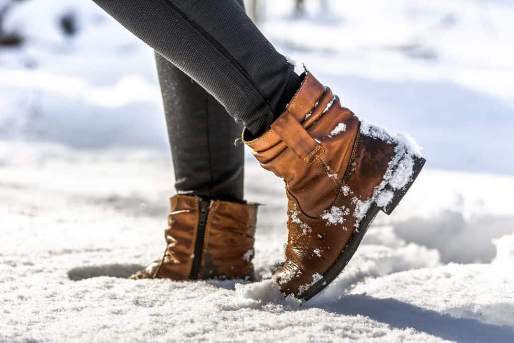 An up close photo of a woman wearing boots while walking on the snow