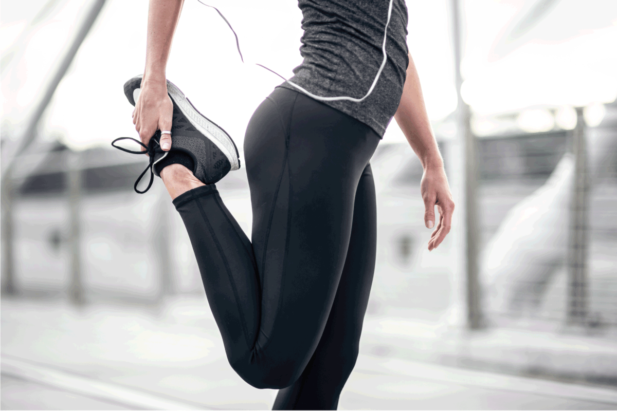 Athletic female figure stretching wearing yoga pants