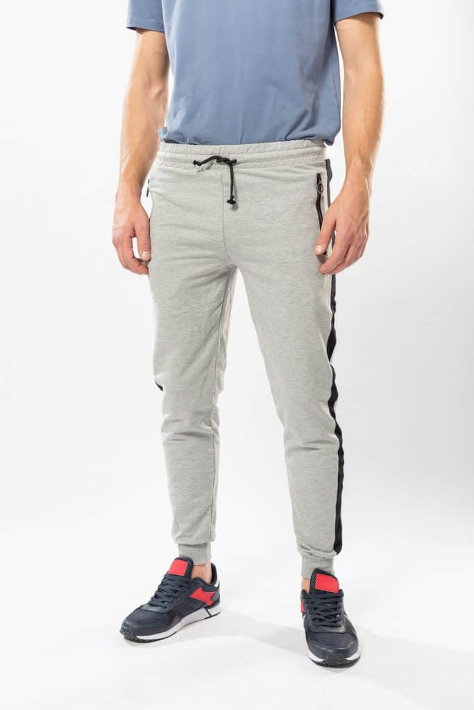 Athletic man in sweatpants and sneakers on a white background