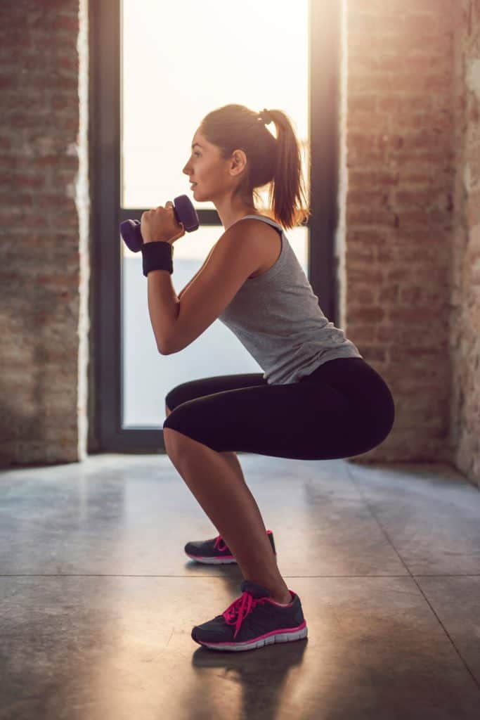 Athletic young woman doing squats with weights.