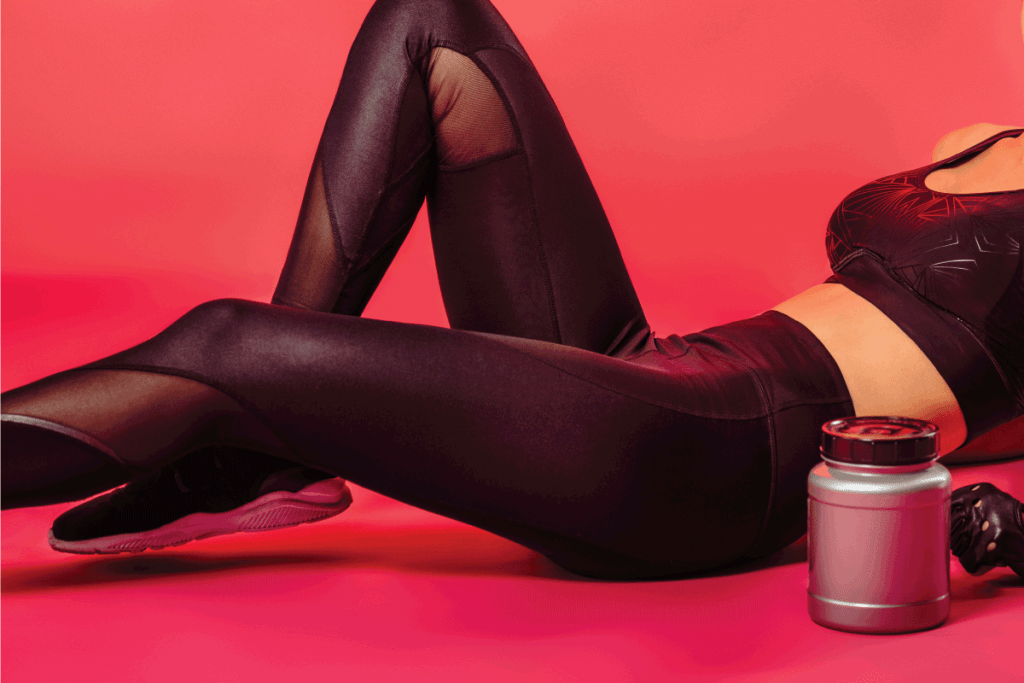 Attractive-sportswoman-lying-with-sport-supplement-jar-on-red.-wearing-black-leggings.-Do-Leggings-Stretch-Or-Shrink-Over-Time