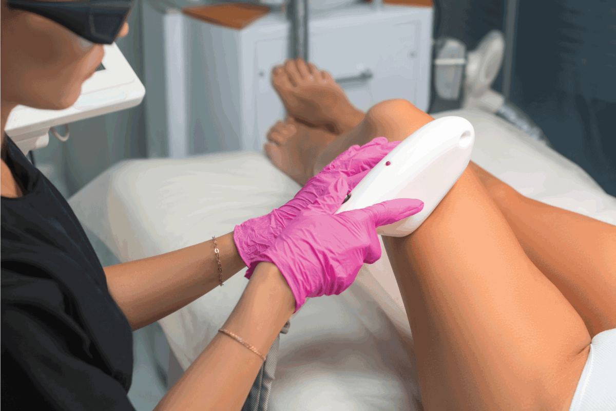 Beautician makes Elos epilation. Leg hair removal procedure.