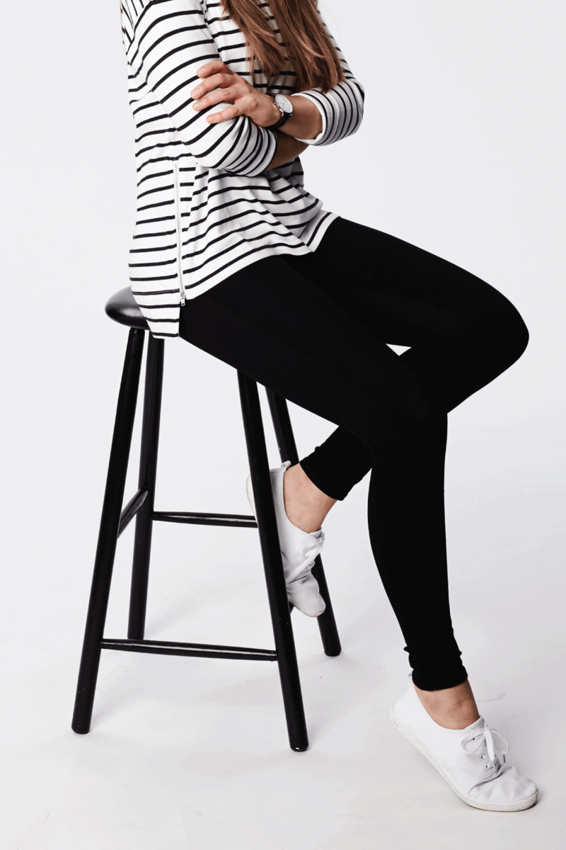 Beautiful brunette on stool, wearing casual attire and black leggings