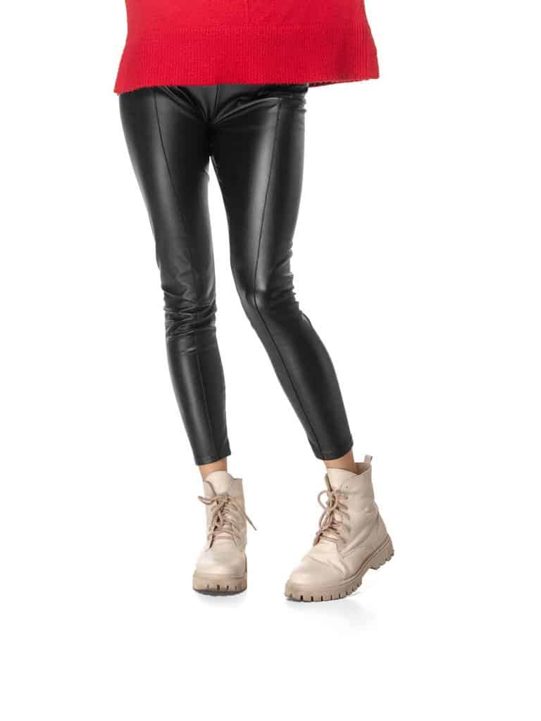 Beautiful female legs in black leggings and boots isolated on white background
