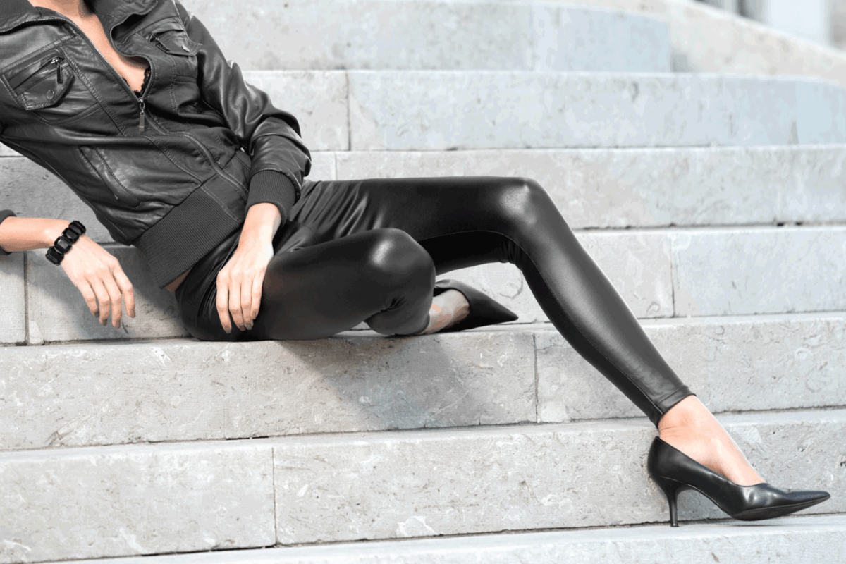 Beautiful woman in a fashionable outfit sitting on stone stairs. chic legging outfits