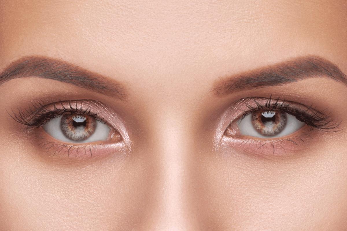 Beautiful woman with long eyelashes, beautiful nude make-up and thick eyebrows. Beautiful eyes close up