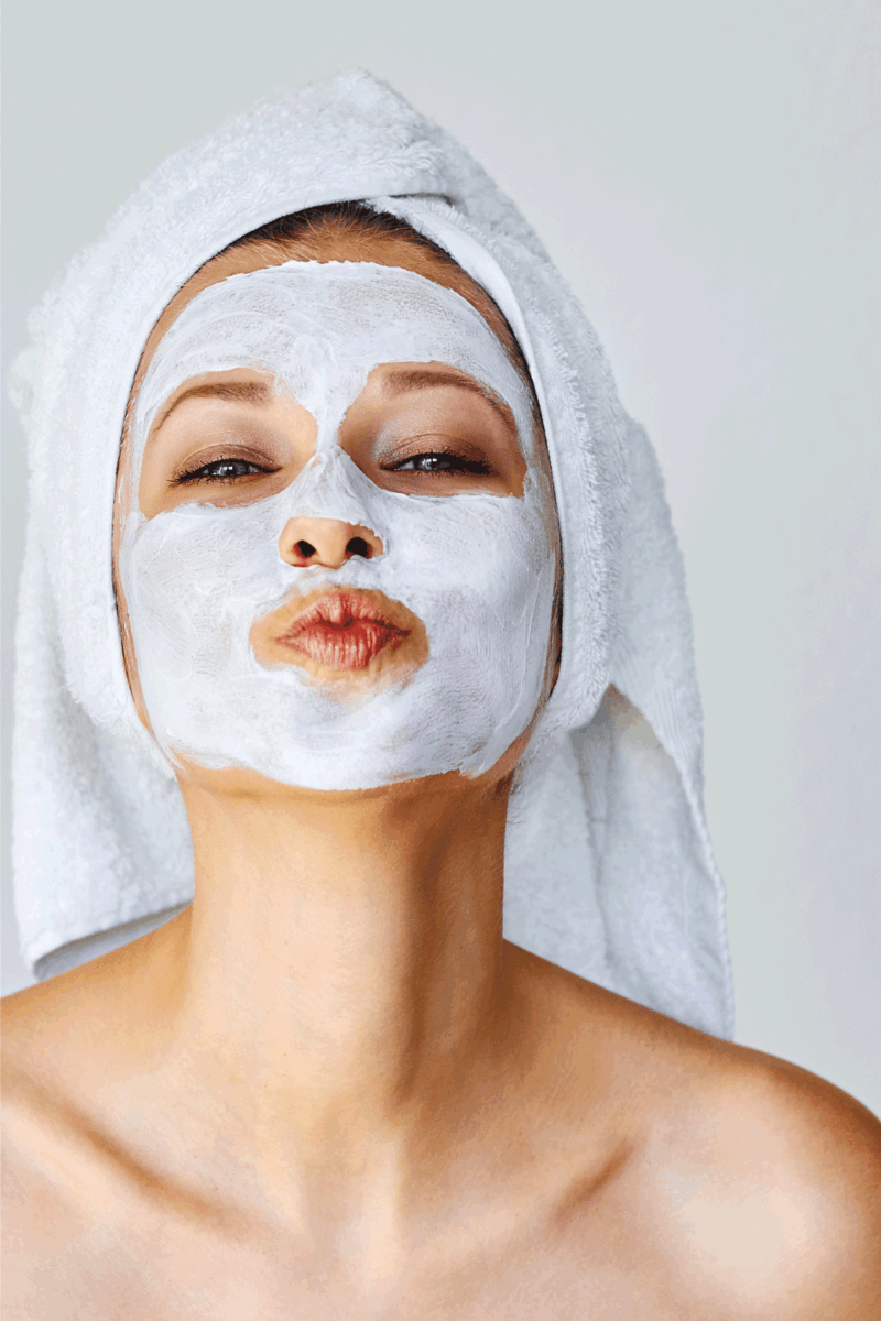 Beautiful young woman with facial mask on her face