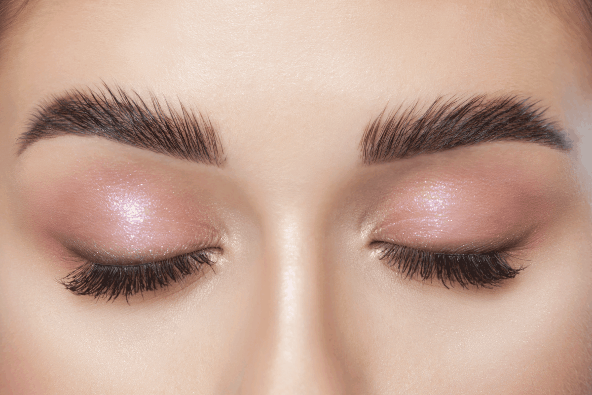 Beautiful young woman with long eyelashes, beautiful fresh nude make-up, thick eyebrows and with clean skin in a beauty salon