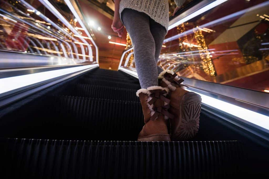 Close up of female legs on escalator in shopping centre