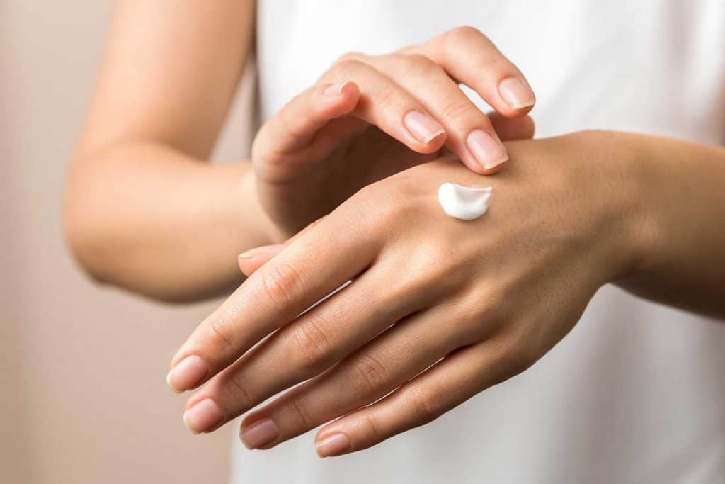 Close up view of woman hand moisturizing them with cream