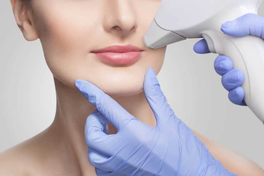 Cosmetologist doing laser hair removal of unwanted hair of the face to a young girl in a beauty salon, Can You Shave Or Pluck Between Electrolysis Treatments?
