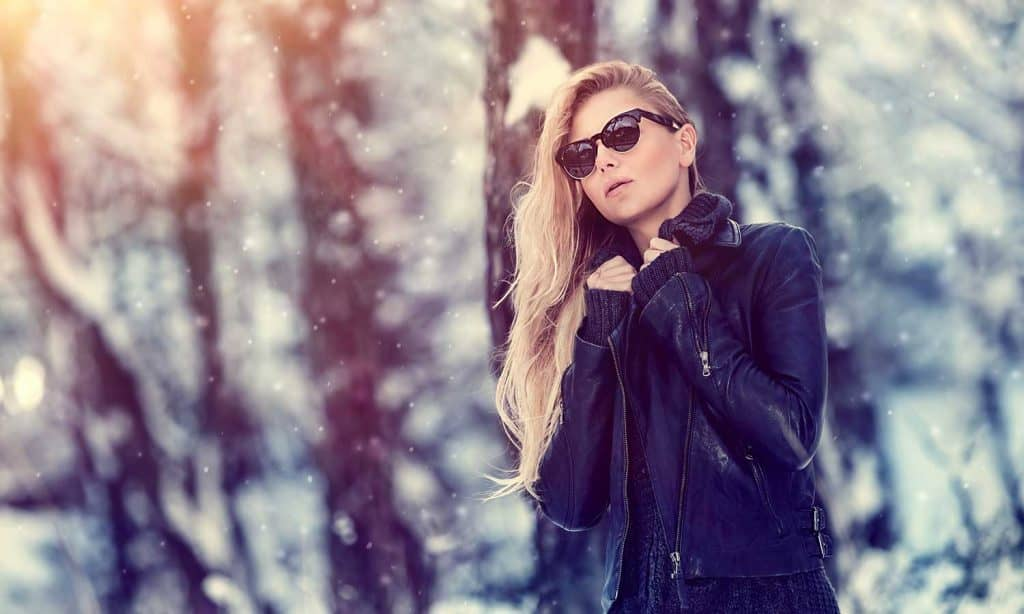 Fashion woman wearing leather jacket posing in the forest
