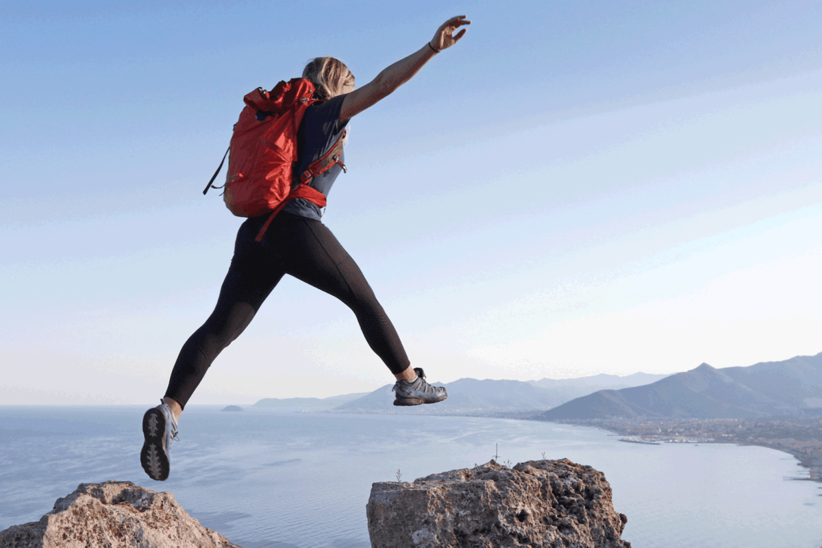 Female hiker jumps between rock summits