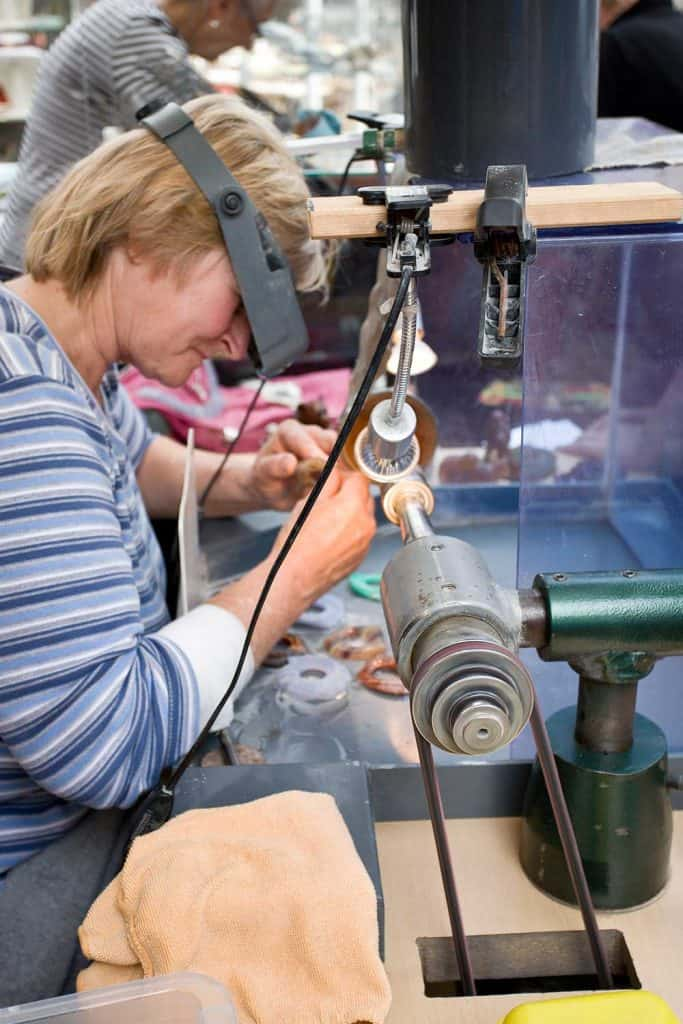 Female lapidary at work on a grinding machine