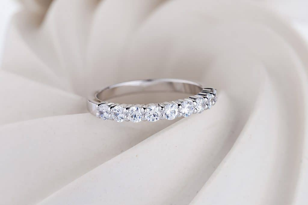 Female pave diamonds wedding ring on white spiral background. Engagement ring with gemestones