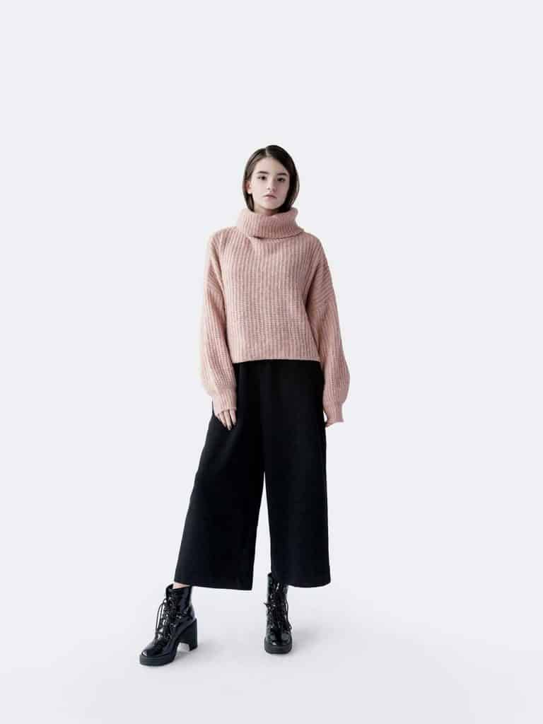Full length portrait of beautiful young brunette woman wearing pink oversized sweater and black pants