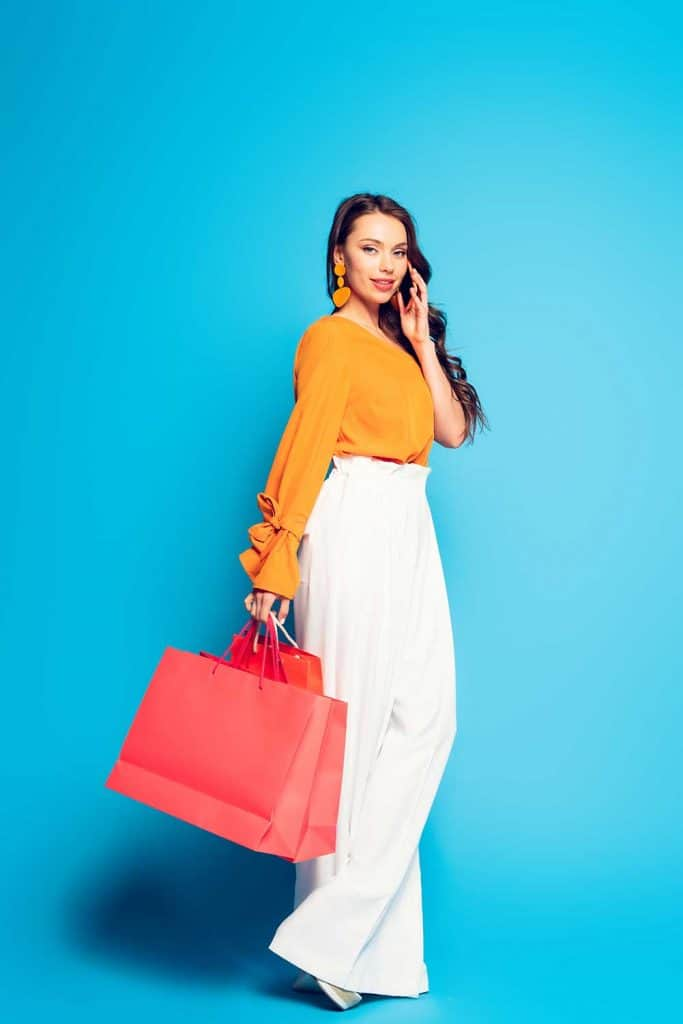Full length view of stylish, smiling woman holding pink shopping bags while touching hair on blue background