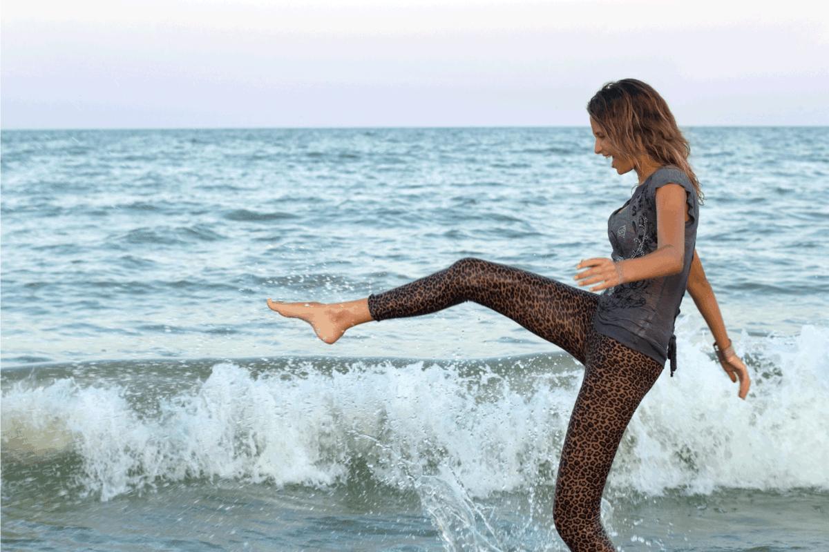 Girl having fun in the sea while wearing leggings