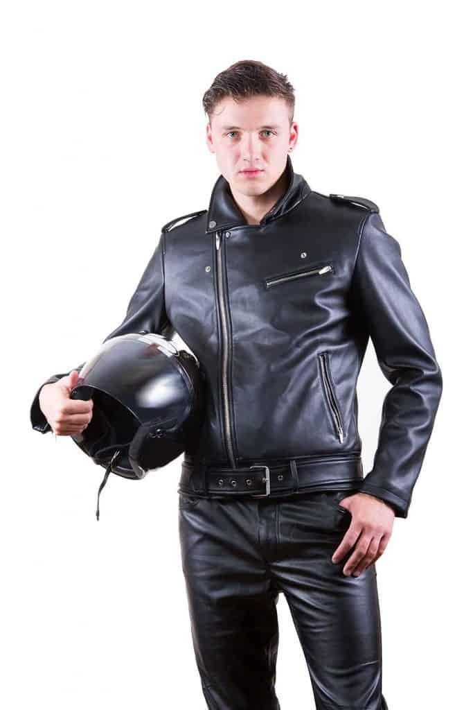 Handsome biker wearing black leather jacket holding motorcycle helmet