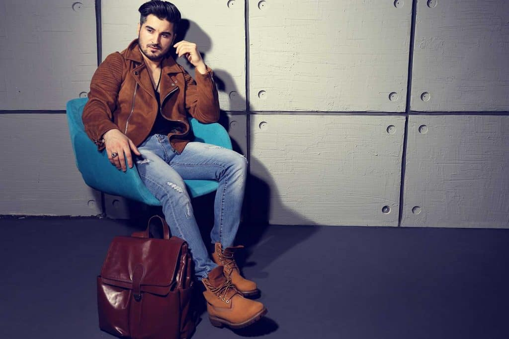 Handsome man on jeans and leather jacket posing