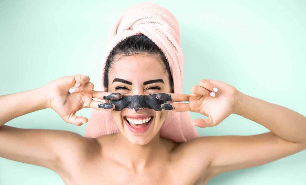 Happy smiling girl applying facial charcoal mask portrait