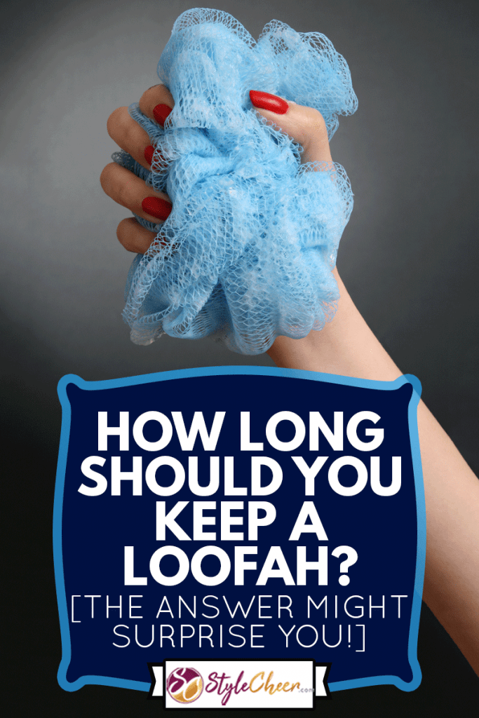 Woman hand holding blue loofah isolated in black background, How Long Should You Keep A Loofah? [The Answer Might Surprise You!]