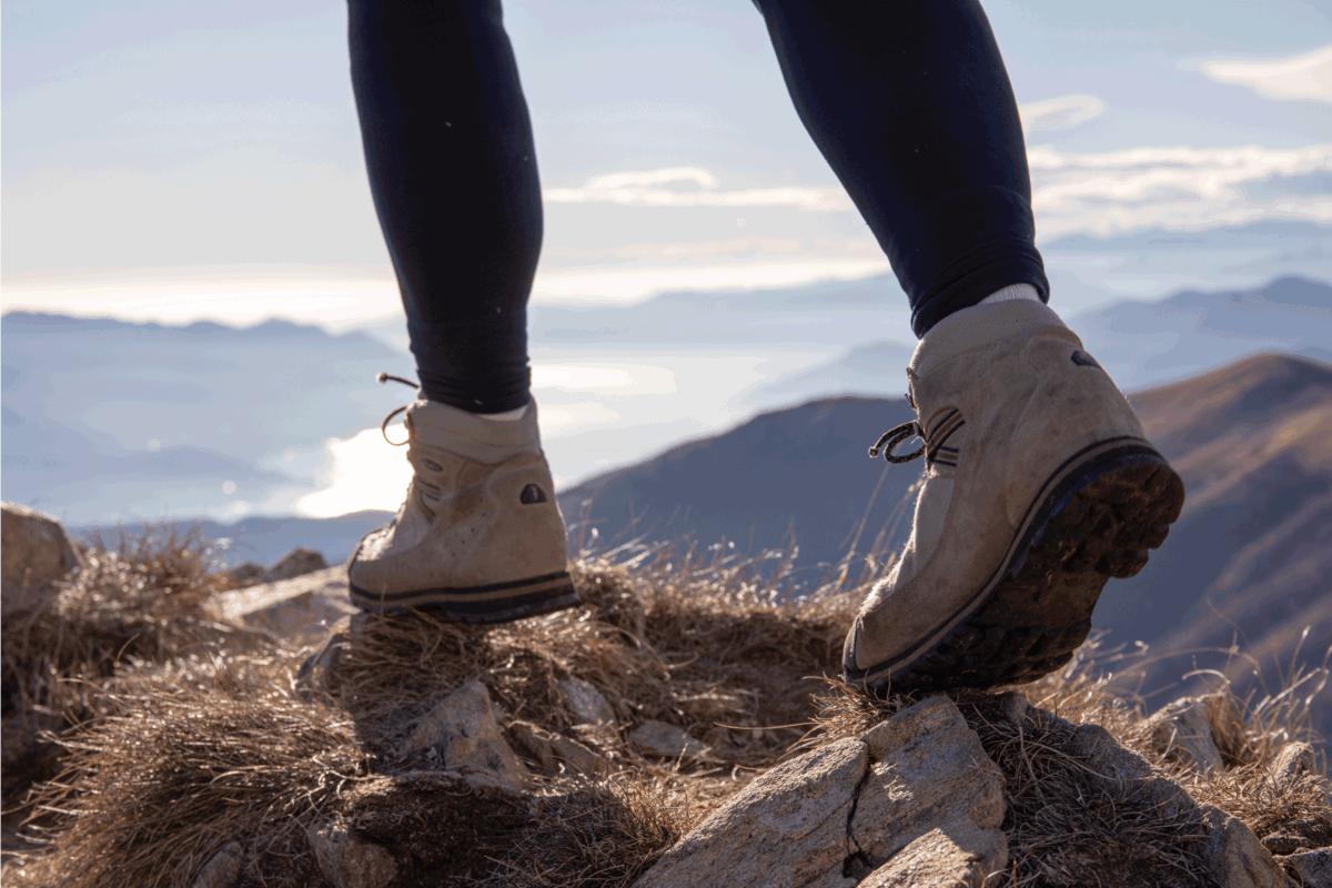 Lake and mountain range distant, climber wearing black leggings